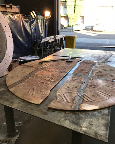 The sundial face lays in pieces waiting to be welded back into one solid peice.